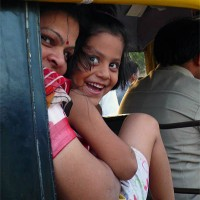 Mother and daughter riding in an Auto Rickshaw in Jalgaon, India. An Auto Rickshaw is a motorized three wheeled cart and version of a traditional rickshaw for hire
